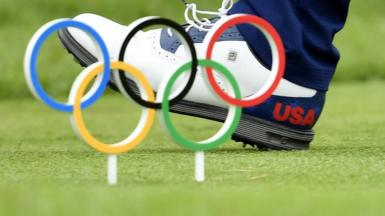 A US golfer walks past a model of the Olympic rings embedded in the course at Tokyo 2020