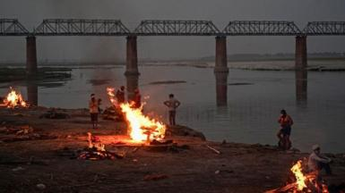 Funeral pyres are lit by the Ganges in Allahabad - bodies have been washing up downstream for days