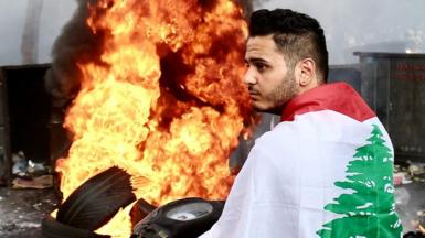Person with Lebanese flag in front of burning tyres, 15 July 2021