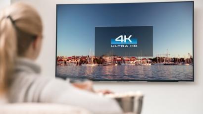Mujer viendo un televisor en 4K.