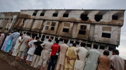 Residents stand outside a garment factory that caught fire the day before, in Karachi September 13, 2012.