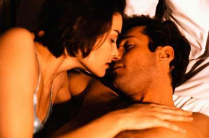 Una mujer y un hombre se besan en la cama