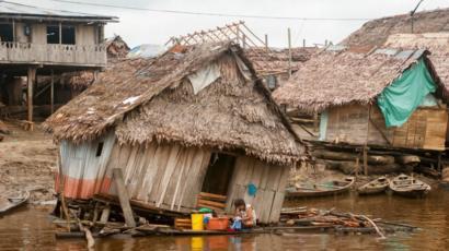 Casas de madera se derrumban sobre el agua.
