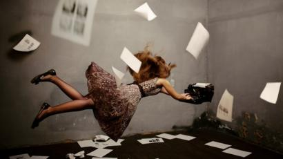 Surreal concept image: a young woman writing, suspended in mid-air, typing on a flying typewriter. There are pages on the floor and floating in the air around her.
