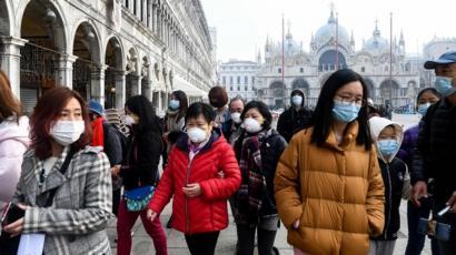 Turis menggunakan masker ketika mengunjungi Piazza San Marco di Venice, Italia
