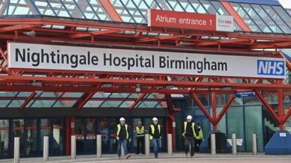 A photo shows three construction workers leave the Nightingale Hospital Birmingham