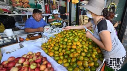 Mulher comprando frutas em feira livre