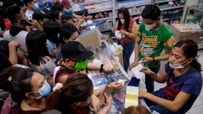 People buying face masks in a pharmacy in Manila