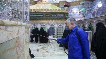 Petugas menyemprotkan disinfektan di kuil Hazrat Masumeh di kota Qom