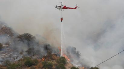 A helicopter drops water to help extinguish the Bobcat fire in Arcadia, California (13 September 2020)