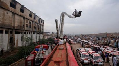 Ambulances and fire brigade vehicles outside a building, after a fire at a garment factory in Karachi September 12, 2012.