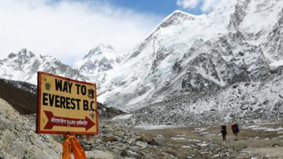 Dos montañistas en una ruta hacia la cumbre del Everest y un cartel que señala