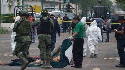 Militares mexicanos y personal forense en una escena de crimen en la ciudad de Nuevo Laredo, estado de Tamaulipas.