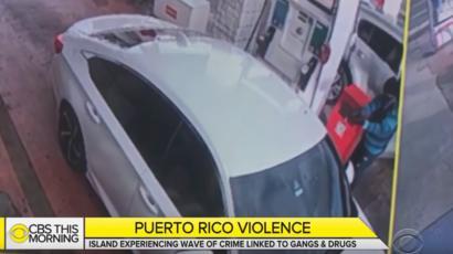 imagen de un encapuchado disparando a otro hombre en un vehículo.