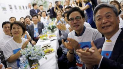 كوريون يشاهدون لقاء ترامب مع كيم في مقر الرابطة الكورية بسنغافورة