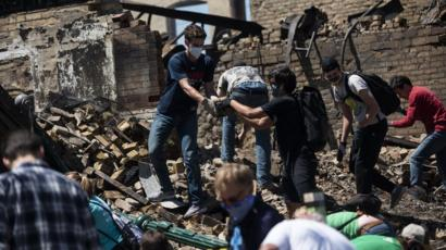 People hand rubble to each other in the ruins of a burned building in Minneapolis