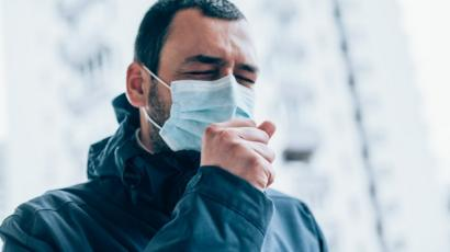 Persona con mascarilla estornudando.