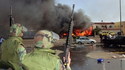 Dos soldados observan como se quema una casa en Los Ángeles.