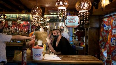 Bar staff check patrons' ID at Under the Volcano in Houston, Texas, on May 22, 2020