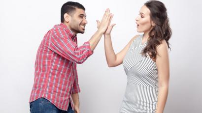 Un hombre y una mujer chocan las palmas.