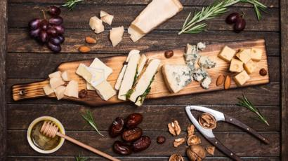 A beautifully laden cheese board, surrounded by almonds, red grapes, dates, honey, rosemary sprigs and walnuts