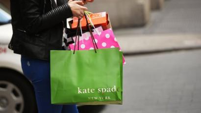 Kate Spade shopping bag held by a shopper