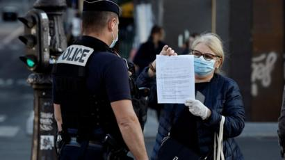 "A police officer checks a woman""s self-certified note for being out before a two minute commemoration near the Notre-Dame Cathedral in Paris at 8 o""clock, on April 15, 2020"