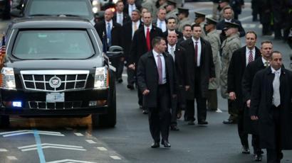 Proteção de agentes do serviço secreto em volta da limusine do presidente