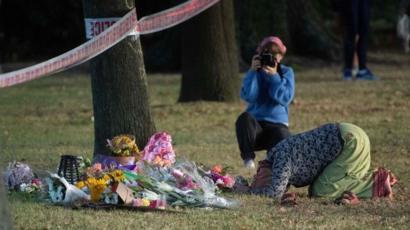 Una mujer reza ante las flores dejadas como homenaje a las víctimas de la mezquita.