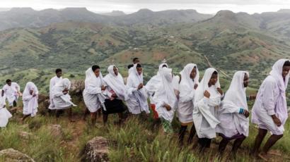 Feligreses de la Iglesia Bautista de Nazareth suben la montaña sagrada Nhlangakaz.