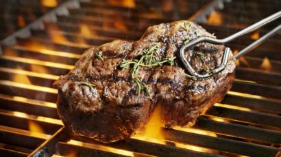 A beef steak over a flame grill