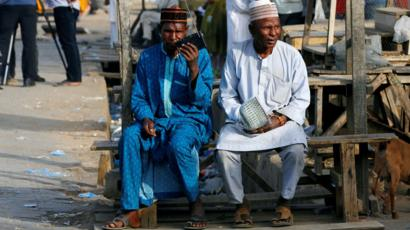 Two men listen to the radio as Nigerians await the results of the Presidential election, in Kano, Nigeria February 24, 2019.