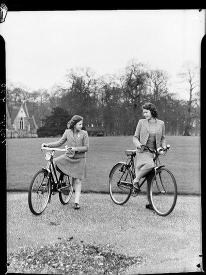 Princess Margaret Rose (1930 - 2002) and Princess Elizabeth (right) preparing to set out on bicycles in the grounds of the Royal Lodge, Windsor, Berkshire