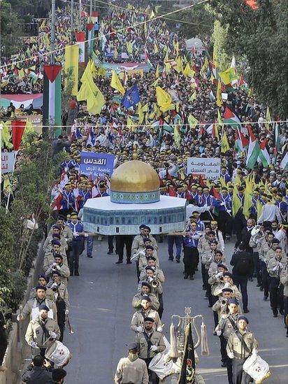 Lebanese demonstrators march with a model of the Dome of the Rock, along with their national flags and Palestinian flags as well as the yellow banners of the Shia movement Hezbollah during a protest in the capital, Beirut, on 11 December 2017