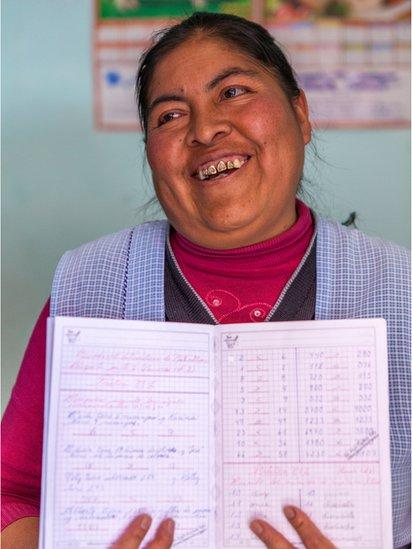 A student proudly holds up her notebook
