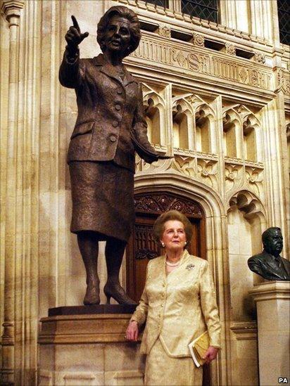 Y Farwnes Thatcher o flaen y cerflun efydd iddi ym Mhalas Westminster