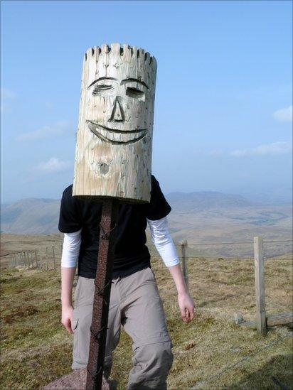 Grant posing behind a carved wooden post