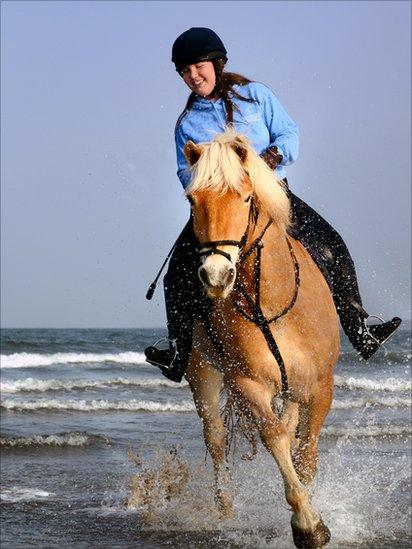 Charlotte riding horse Solo along the beach
