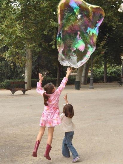 Two girls jumping up to touch a bubble