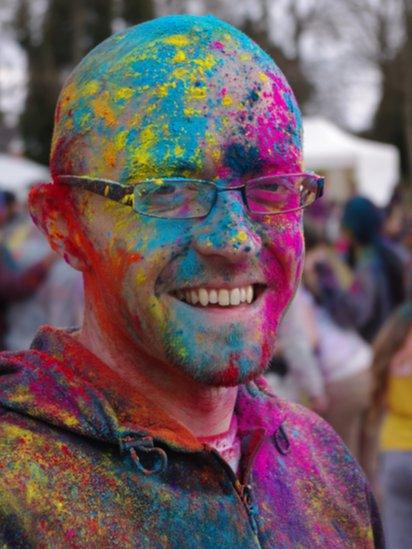 Man covered in brightly coloured powder