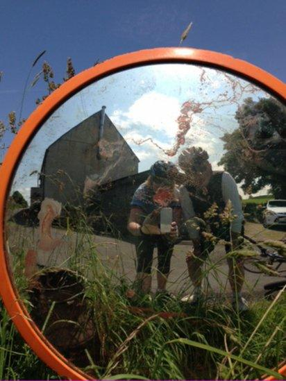 Cyclists' reflection in a mirror