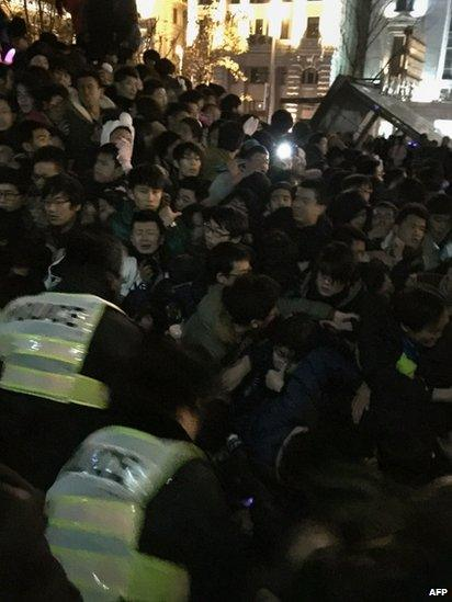 Policemen try to help revellers trapped in a stampede as people gather on Shanghai's historic riverfront to welcome in the new year on 31 December 2014