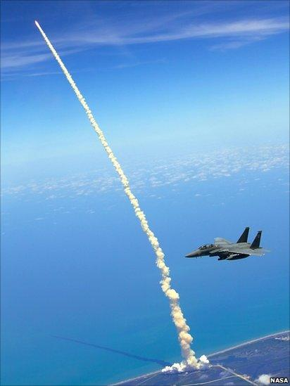 An F-15E Strike Eagle flies past as the Space Shuttle Atlantis (STS-132) launches from Kennedy Space Center, 2010