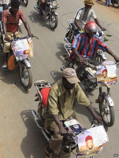 Men ride motorcycles bearing posters of Chukwuemeka Ojukwu
