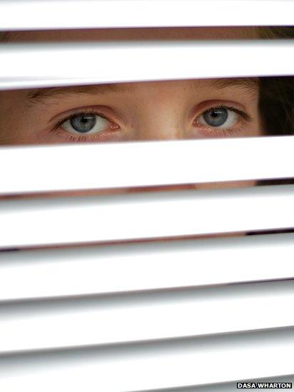 Girl looking through blinds