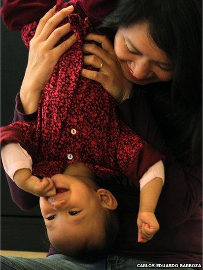 Girl being held upside down by mum