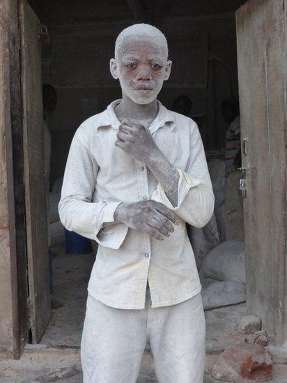A man covered in dust from a mill