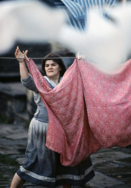 إمرأة تعلق ملابسها المغسولة على حبل للتجفيف