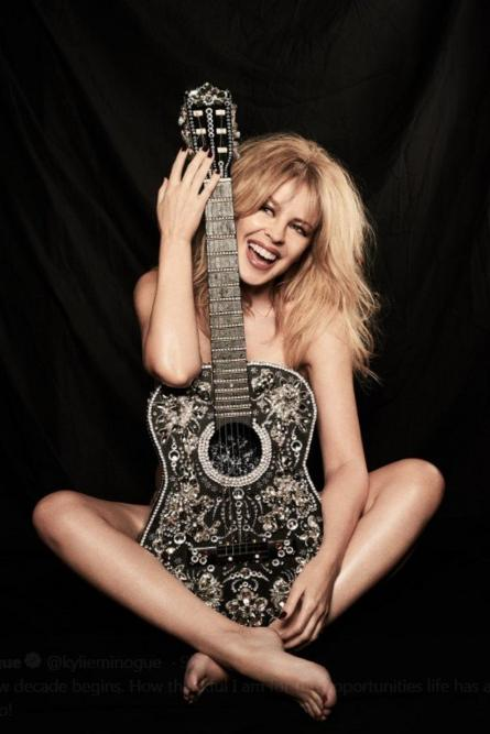 Kylie Minogue sits naked behind a decorated guitar. Date unknown