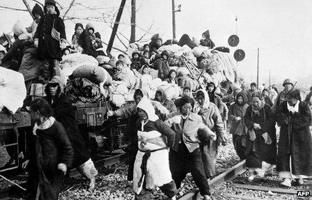 Korean refugees head south on board flatbed trains from Pyongyang in 1951.